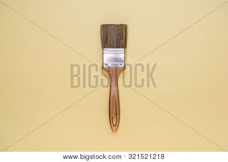 Brush With A Golden Hilt On A Yellow Background. Minimalism, Place For Text, Top View.