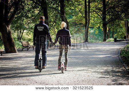 Vilnius, Lithuania - September 30, 2018: Young Couple Rides Unicycles In Bernardinai Park, A Popular