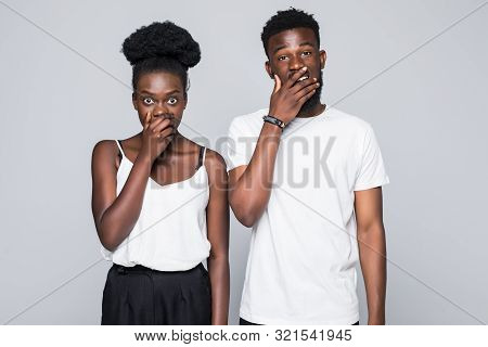 African Couple In Denim Shirts Covering Their Mouths While Looking At The Camera Over Grey Backgroun