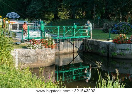 People Preparing River Locks On The River Oust Near Josselin For Houseboats To Pass Through