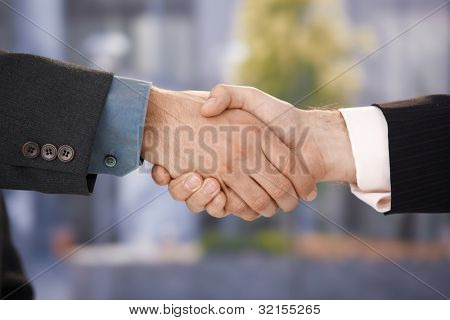 Closeup photo of business handshake, businessmen shaking hands, agreement, greeting, success.