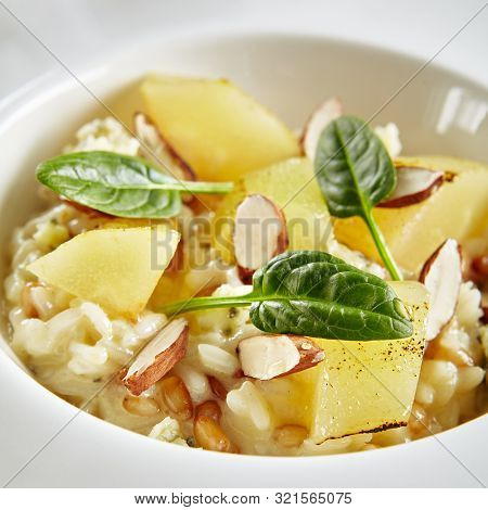 Exquisite Serving White Restaurant Plate of Risotto with Gorgonzola Cheese, Raisins, Almonds and Baked Pear Close Up. Beautiful Delicacy Italian Fruit Paella on Dark Stone and Leaves Background