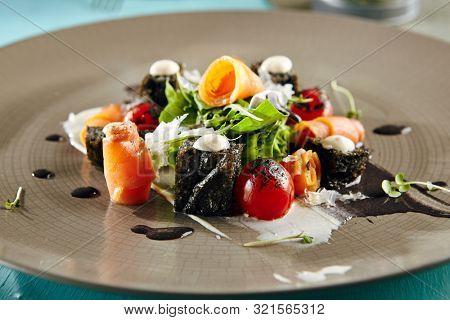 Restaurant Salad Food - Black Caesar Salad with Smoked Salmon. Gourmet Restaurant Salad Menu. Salad Garnished with Rucola, Leaves and Vegetables