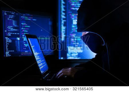 Man In Hood And Mask Is Hacking Password, Phishing. Programmer Developer Is Writing Code Malware Sof