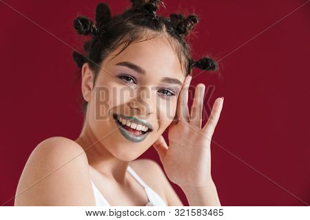 Image of adorable punk girl with bizarre hairstyle and dark lipstick smiling at camera isolated over red background poster