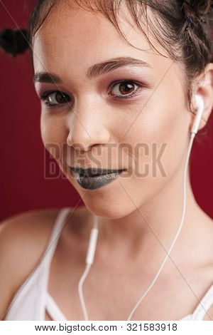Image of young punk girl with bizarre hairstyle and dark lipstick listening to music with earphones isolated over red background poster