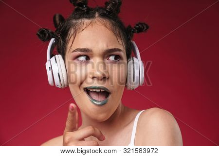Image of young punk girl with bizarre hairstyle and dark lipstick grimacing while listening to music with headphones isolated over red background poster