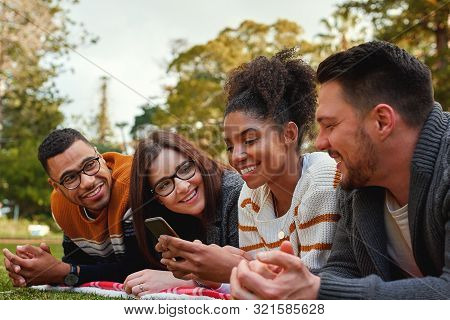 Group Of Happy Diverse Friends Looking At African American Woman Using Her Mobile Phone In The Park