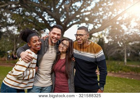 Smiling Group Of Friends Laughing Together While Standing With Arms Around Each Other At A Park - Ha