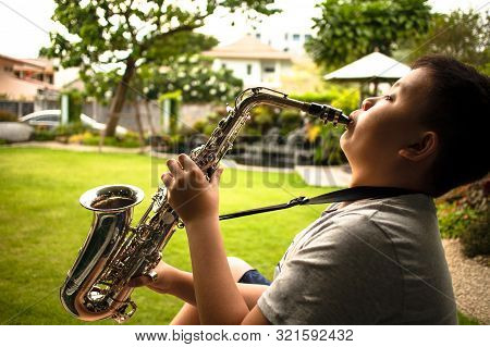 Sideview Of Asian Young Boy Playing Saxophone At Courtyard