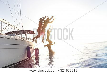 Side View Of Young Millennial Friends Jumping From Sailboat On Sea Ocean Trip - Guys And Girls Havin