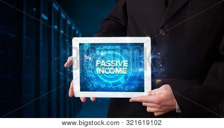 Young business person working on tablet and shows the inscription: PASSIVE INCOME, business concept poster