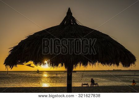 A Silhouette Of A Palapa At Sunset On Palm Beach In Aruba