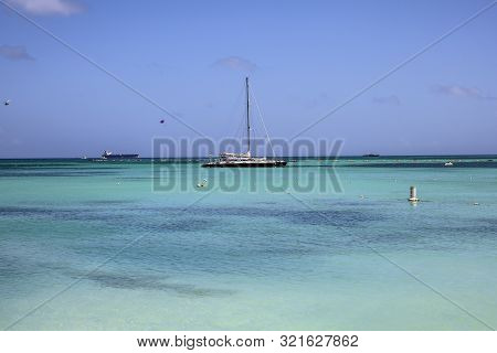 A Sail Boat Floats On The Crystal Clear Water Of The Caribbean Sea