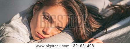 Tired woman in the morning waking up in bed unhappy. Funny expressive Asian girl lazy can't get up feeling exhausted or depressed. Home lifestyle banner panorama.
