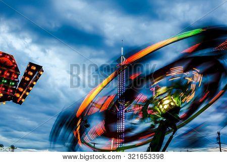 Evening amusement par ride with dark dramatic sky