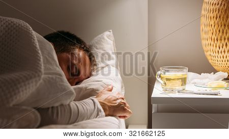 Sick Man Sleeps Covered With A Blanket Lying In Bed With High Fever, Resting At Living Room. He Is E