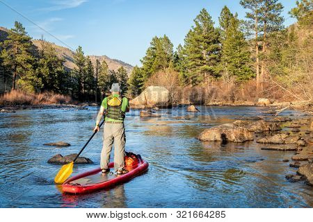 senior male paddling inflatable stand up paddleboard through rock garden on a mountain river - Poudre RIver in Colorado in spring scenery with low water flow