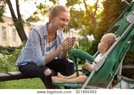 Teen Nanny With Cute Baby In Stroller Playing In Park