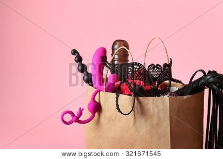 Paper Shopping Bag With Different Sex Toys On Pink Background
