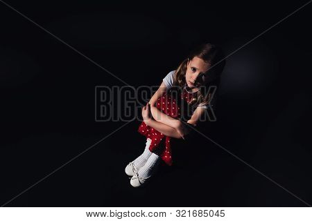 Sad, Scared Child Sitting On Floor And Looking At Camera On Black Background