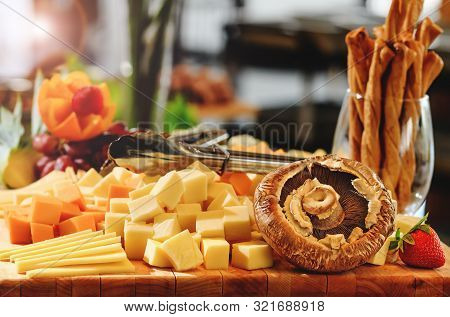 Rustic Mix Of Cheese Cuts, Mushrooms And Fruits On A Wooden Platter, During Brunch Buffet. Tasty Ass