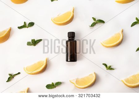 One Bottle Of Essential Oil Surrounded With Fresh Herbs Green Mint Leaves And Lemon Lobules. Flat La