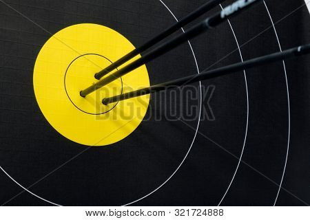 Three arrows in the center of black and yellow archery target. Accuracy and precision concept.
