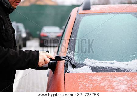 Man Clears Snow From Icy Windshield Of Car. Scraper In Mans Hand. Cleaning Frozen Window Of Orange A