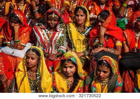 PUSHKAR, INDIA - NOVEMBER 21, 2012: Unidentified Rajasthani girls in traditional outfits prepare for dance perfomance at annual camel fair Pushkar Mela in Pushkar, Rajasthan, India