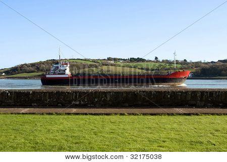 Cargo Ship Sailing Past Sea Wall