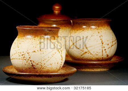 ceramic teapots with saucers on black background