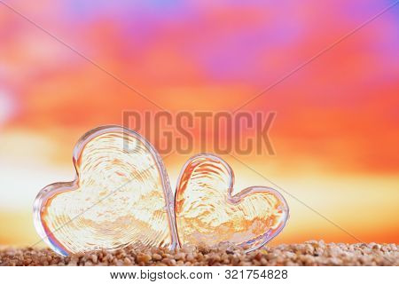 clear heart sea glass  on  beach sand   with bright sunrise or sunset background