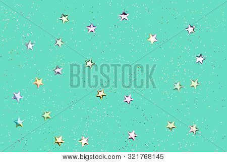 Green Mint Background With Holographic Glitter And Metallic Stars. Flat Lay Style