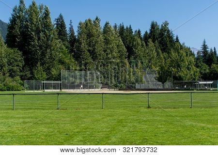 Empty Baseball Or Softball Diamond From The Back Fence And Foul Line Looking Towards The Grass And T