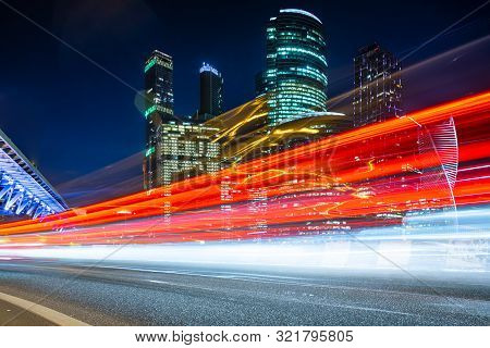 Modern Office Buildings With Light Trails Of Night Traffic