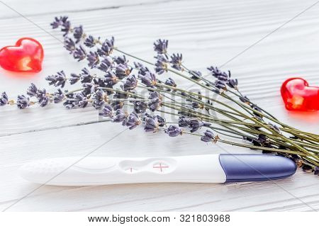Positive Pregnancy Test With Lavender On Wooden Background