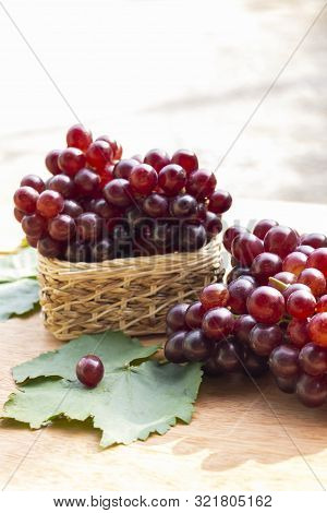 Ripe Red Grape With Leaves Which Fruit Fresh In Basket On A Wooden Table Background.