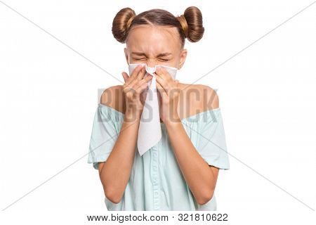 Portrait of unhealthy sick teen girl with napkin close her nose from allergy or rhinitis. Unhappy ill child suffering from running nose and sneezing and blow her nose isolated on white background.