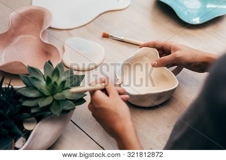 Hands Of Ceramist Painting A Bowl In Studio