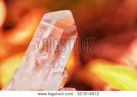 Quartz Crystal On Background Of Bonfire Coals And Burning Fire Orange Color . Beautiful Gem Chalcedo