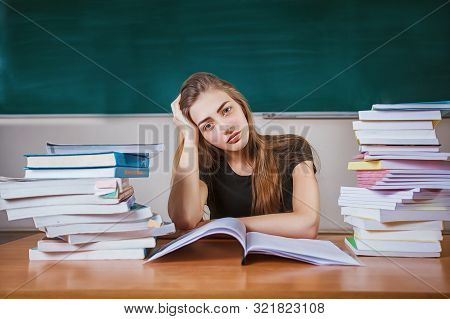 Frustrated Female Student Sitting At The Desk With A Huge Pile Of Study Books In Classroom. Young Co