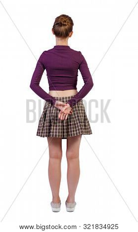 back view of standing young beautiful woman. girl watching. Rear view people collection. backside view of person. Isolated over white background. A girl stands clasped hands behind her back.