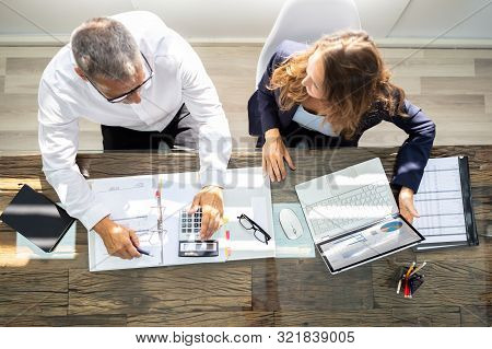 An Overhead View Of Two Businesspeople Calculating Invoice In Office While Using Laptop