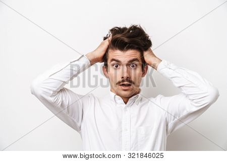 Portrait closeup of shocked mustached man wearing shirt looking at camera and grabbing his head isolated over white background