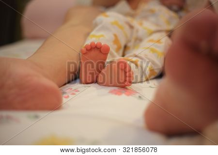 baby struggling agonizingly between mother's legs while being tend to. baby feet wrenching to no avail.  poster