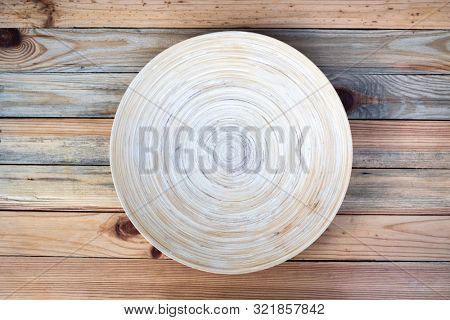 Round bamboo plate on a wooden table closeup. Food photography background