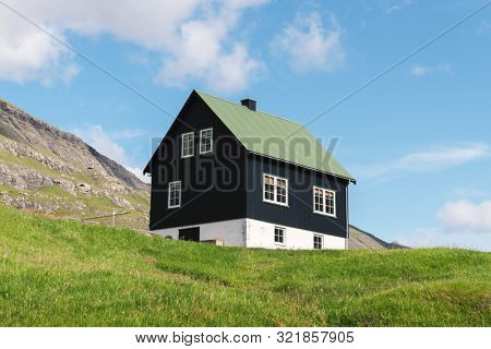 Simple house with green roof on blue sky background