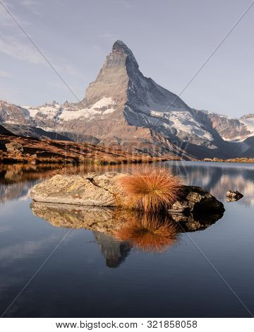 Picturesque landscape with colorful sunrise on Stellisee lake. Snowy Matterhorn Cervino peak with reflection in clear water. Zermatt, Swiss Alps