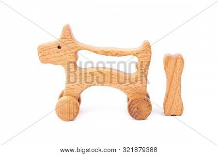 Photo Of A Wooden Dog With Bone On Wheels  Of Beech. Toy Made Of Wood  On A White Isolated Backgroun